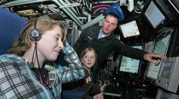 003_Sonar_Technician_1st_Class_Billy_Trowbridge_points_out_several_features_of_the_control_room_to_Elizabeth_Godin_and_Elizabeth_Palczynski-672x372