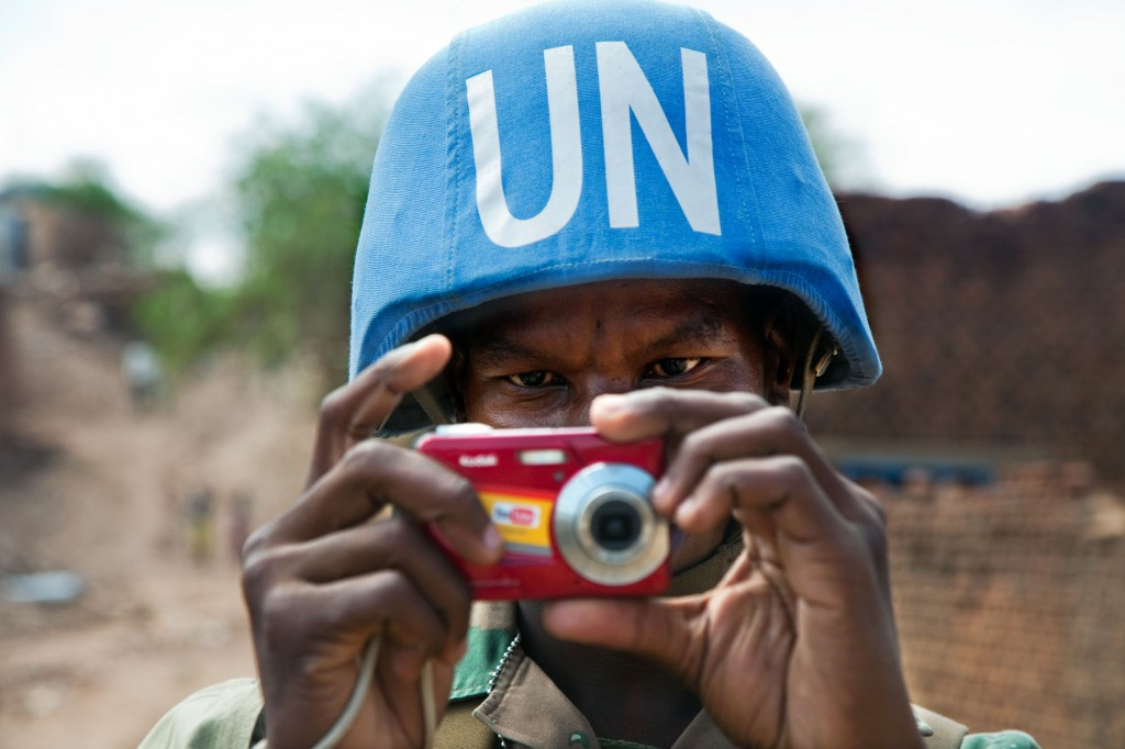 A South African peacekeeper snaps a photo with a digital camera during a patrol in Darfur, Sudan. U.N./Albert Gonzalez Farran photo
