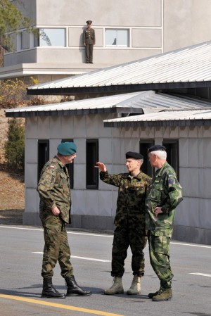 "Brigadier General Andrzej Przekwas from Poland, Major General Jean-Jacques Joss from Switzerland and Major General Christer Lidstrom from Sweden talk as a North Korean soldier (top) stands guard before a meeting of the Neutral Nation Supervisory Commission (NNSC) at the truce village of Panmunjom in the demilitarized zone dividing two Koreas on April 8, 2009. North Korea warned of ""strong steps"" if the United Nations censures its rocket launch, hours after releasing triumphal footage of what Pyongyang describes as a peaceful space programme."