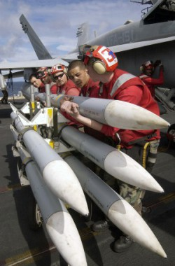 Aviation Ordnanceman Third Class (AO3, left) William Cinco, AO3 Bobby Rainwater, AO1 Phil Camp, AOAN Chris Rangel and AOAN Jeremy Roth of VFA-151 prepare to install an AIM-120 AMRAAM (Advance Medium Range Air to Air missile) on to an F18 Hornet aboard the USS Constellation (Photo: Felix Garza Jr., 29.11.2002).