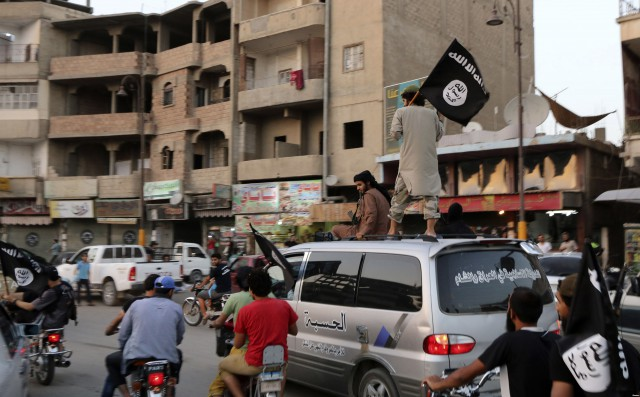 Members loyal to the ISIS wave their flags as they drive around Raqqa ind June 29, 2014.