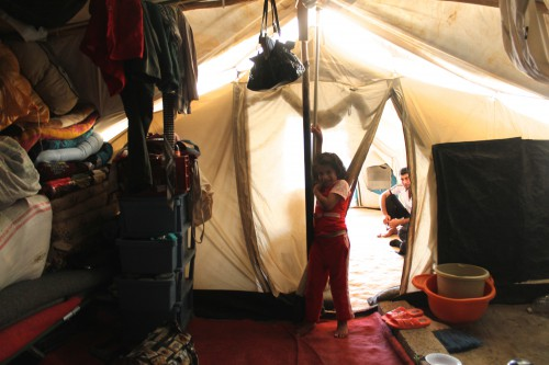 A young girl plays in one area of her family's cramped tent in Kawergosk Syrian refugee camp, Iraqi Kurdistan, as the adults discuss recent gains by the extremist group ISIS in northern Iraq (Photo: Sophia Jones).