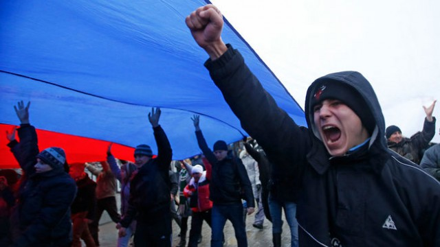 Protesters march under a huge Russian flag in Simferopol, Crimea.