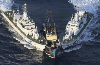 "A Chinese boat is surrounded by Japan Coast Guard patrol boats after activists descended on Uotsuri Island, one of the islands of ""Senkaku"" (Japanese) and ""Diaoyu"" (Chinese), in the East China Sea (Photo: Yomiuri Shimbun, Masataka Morita / AP)."