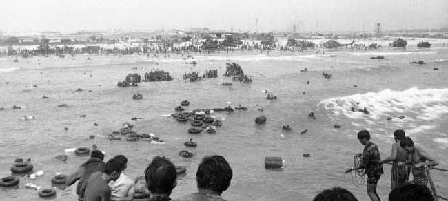 South Vietnamese marines line beaches and swim out to ships, fleeing from the northern port city of Da Nang on March 29, 1975 before its fall to the Viet Cong and north Vietnamese. This picture was taken as some marines successfully fled, abandoning scores of weapons, vehicles and even a helicopter. In the foreground, men on LSTs (Landing Ship, Tank) prepare to throw rope to marines coming up on inner tubes. Only a fraction of the city's 100,000 defenders were evacuated before its fall.
