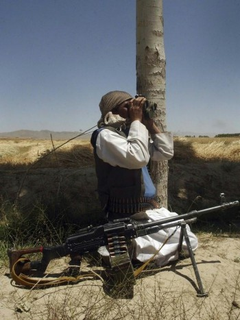 A Taliban fighter looks through binoculars in an undisclosed location in Afghanistan on July 14, 2009.