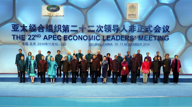 Chinese President Xi Jinping and his wife Peng Liyuan pose for a group photo with participants of the 22nd APEC Economic Leaders' Meeting and their spouses ahead of a welcome banquet in Beijing, capital of China, Nov. 10, 2014.