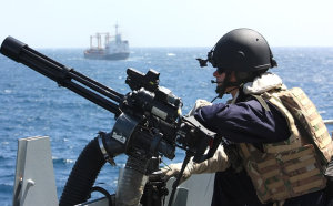 A Royal Navy gunner surveys the horizon for pirate activity from HMS Northumberland