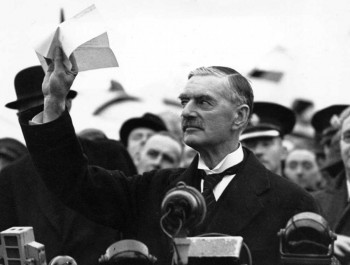 Appeasement: Neville Chamberlain holding the paper containing the resolution to commit to peaceful methods signed by both Hitler and himself on his return from Munich.