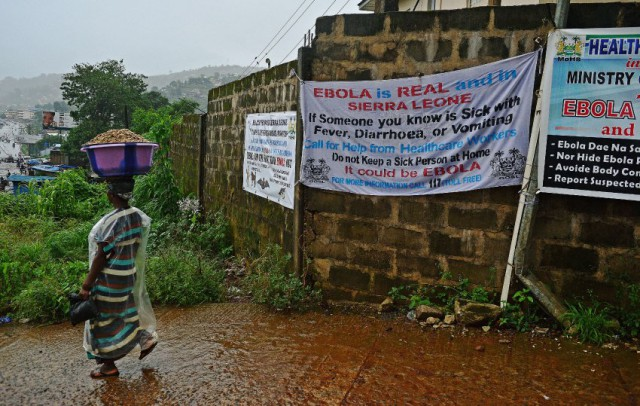 A woman walks past signs warning of ebola in Freetown, Sierra Leone on August 13, 2014 (Photo: Carl de Souza).