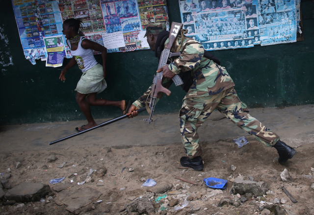 A Liberian soldier in the Ebola Task Force tried to enforce a quarantine in August 2014 by confronting a woman in Monrovia (Photo:  John Moore).