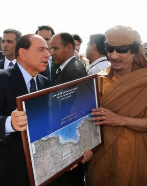 Libyan leader Moamer Kadhafi and Italian Prime Minister Silvio Berlusconi (L) hold a framed map of a highway project during a ceremony to lay its foundation stone in Touisha, 50 kms (31 miles) east of Tripoli, on August 30, 2009. The 1,200 kilometre (750 mile) highway has long been demanded by Libya as compensation for Rome's occupation and colonial rule over the north African country from 1911 until World War II.