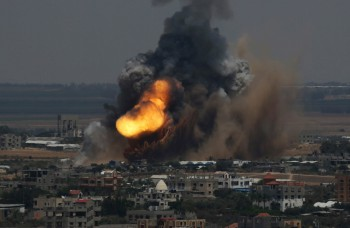 Smoke and flames are seen following what police said was an Israeli air strike in Rafah in the southern Gaza Strip July 8 (Photo: Ibraheem Abu Mustafa / Reuters).