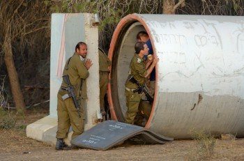 Israeli reserve soldiers go inside a cement pipe used as an air raid bomb shelter in a field along the southern Israeli border with the Gaza Strip, early July 15, when several 'red alert' alerts sounded (Photo: Jim Hollander).