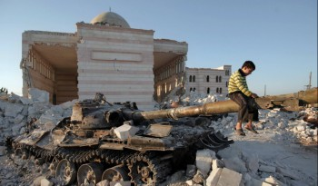 A boy plays on the gun of a destroyed Syrian army tank partially covered in the rubble of the destroyed Azaz mosques, north of the restive city of Aleppo, on Aug. 2, 2012 (Photo: Ahmad Gharabli/AFP/Getty Images).