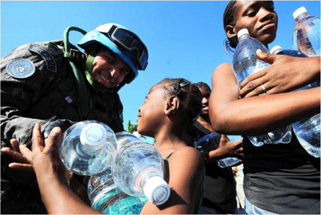 Haitians receive water from Brazilian U.N. peacekeepers at an aid-distribution point by the presidential palace.