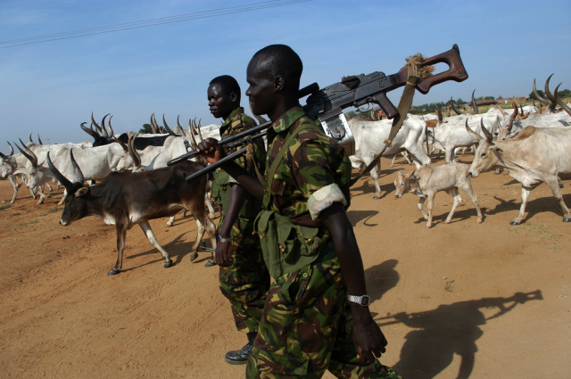 Soldiers from the Sudanese People's Liberation Army (SPLA) escort cattle of the Dinka Bor through Juba.