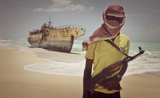 Somali pirate Hassan stands near a Taiwanese fishing vessel that washed up on shore after the pirates were paid a ransom and released the crew, in the once-bustling pirate den of Hobyo, Somalia (Photo: Farah Abdi Warsameh).